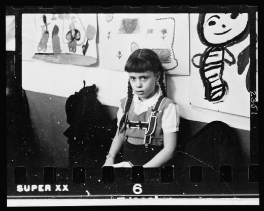 02-7.-Young-girl-half-length-portrait-standing-against-wall-displaying-art-work-in-classroom-in-Chicago-Illinois-520x416