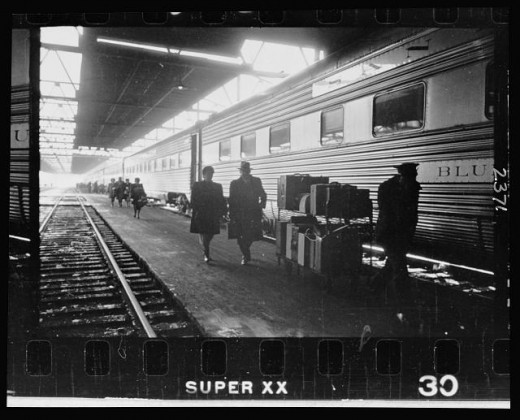 07-2.-A-man-and-a-woman-walking-with-a-porter-on-the-platform-next-to-a-railroad-passenger-car-at-the-train-station-520x420
