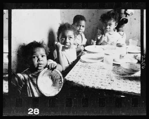 09-18.-African-American-children-seated-around-a-table-in-an-apartment-eating-520x416