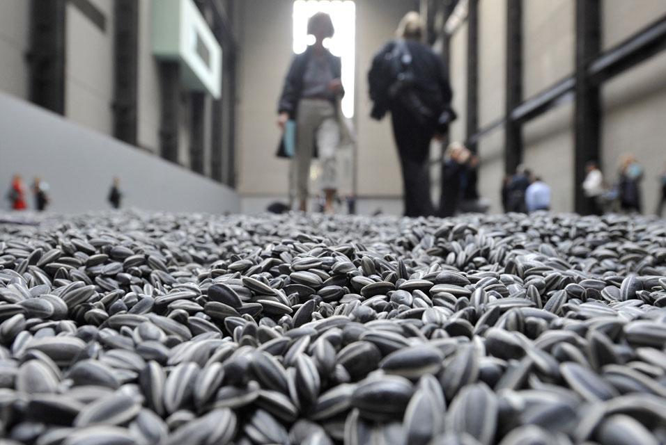 A photo from a low perspective showing sunflower seeds on the floor in the foreground, with out of focus people in the background.