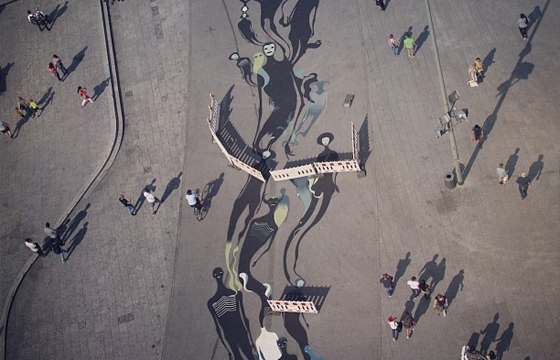 Herbert Baglione paints a stream of silhouettes on plaza floor in Frankfurt, Germany