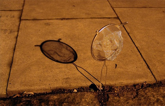 Strainer Shadow Art by Isaac Cordal